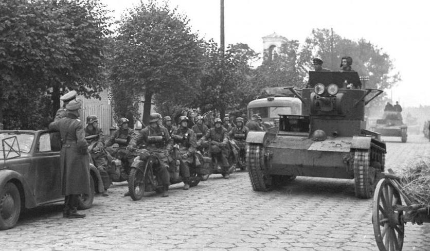German motorcyclists giving a way to rolling Soviet tanks.